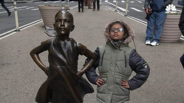 A dark-skinned child in a grey coat stands, hands on hips, to the right of a bronze statue of a child in the same stance.