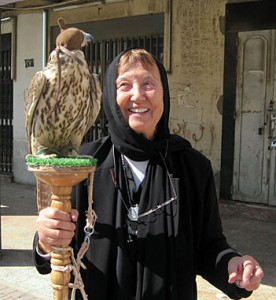 Denise Schmandt-Besserat, a light-skinned person dressed in a black robe with their head covered, holds a wooden perch on which a hooded raptor sits.