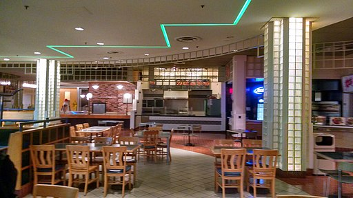Tables and chairs in an empty shopping mall food court, with lighted columns and a turquoise neon zig-zag on the ceiling.