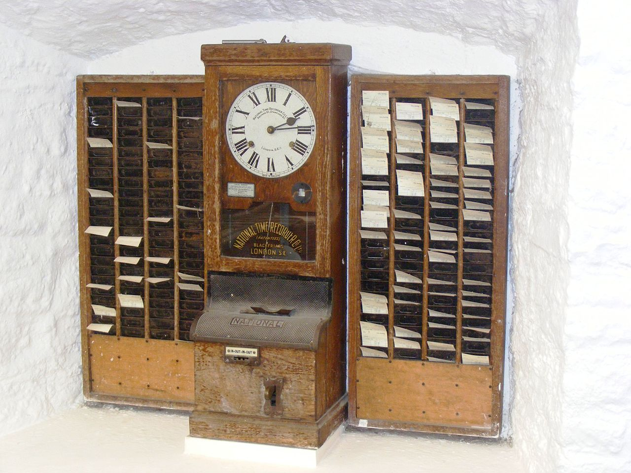 A tall wooden punch-in clock flanked by two wooden file organizers in an arched niche of a whitewashed stone wall. Time clock at Wookey Hole Cave Museum in England, photo by Rodw on Wikimedia Commons.