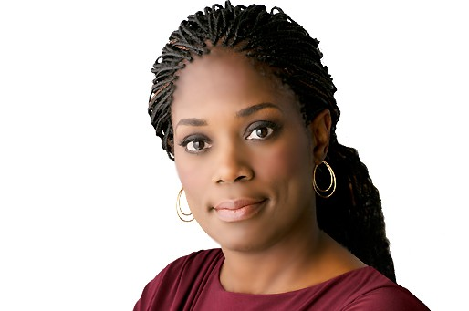 a headshot of Antoinette Tuff, a dark-skinned person with braided hair and a neutral expression wearing a burgundy top and hoop earrings.