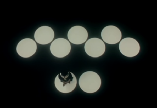 On a black background, an arrangement of seven white dots or spotlights, with another grouping of two white spots below it. A person dressed in black and white stands on the lefthand dot in the bottom arrangement.