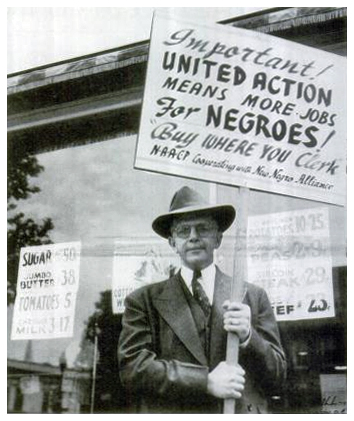 In a black-and-white photo, Walter White, the white executive secretary of the NAACP, stands in front of a grocery window holding a sign calling for boycott of stores with discriminatory hiring practices, as part of the New Negro Alliance's 1933-1943 campaign in Washington, DC. The photographer is unknown. The image is courtesy of The Crisis.