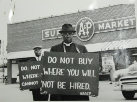 "In a black-and-white photo, two Black men stand in front of an A&P super market holding signs reading ""Do not buy where you will not be hired"" as part of the New Negro Alliance's 1933-1943 boycott against discriminatory hiring practices in Washington, DC. Floyd McKissick Papers (4930), Southern Historical Collection, Wilson Library, UNC Chapel Hill."