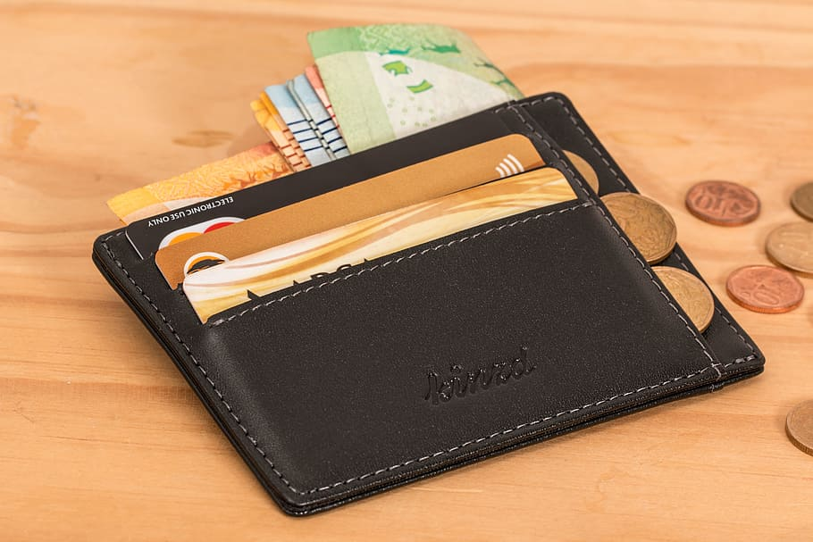 Dark-colored wallet holding bills, cards, and coins on a wooden surface. Image uploaded to Wallpaper Flare by cristine da cruz.